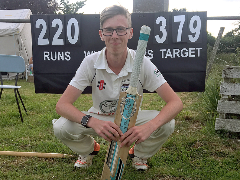 Double Ton Clubber - North Devon's Jay Rothery in front of the scoreboard showing his exploits